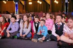 年轻戏迷 热心地观看儿童的圣诞节木偶剧场Smeshariki的孩子 免版税图库摄影