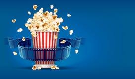 戏院的玉米花和在蓝色背景的影片磁带 图库摄影