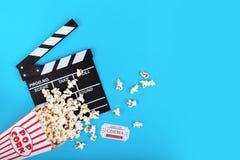 戏院背景 玉米花和clapperboard在蓝色背景 免版税库存照片