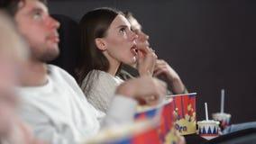 戏院观看的影片饮用的可乐和吃玉米花的朋友 股票录像
