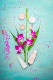 组成与桃红色兰花、奶油和化妆水的温泉或健康在土耳其玉色破旧的别致的背景 库存图片