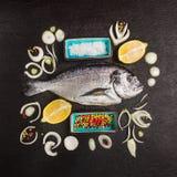组成与dorado生鱼、柠檬和香料在黑织地不很细背景 库存照片