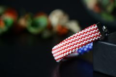 成串珠状在美国国旗的颜色的钩针编织镯子在黑暗的背景的 免版税库存图片