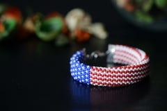 成串珠状在美国国旗的颜色的钩针编织镯子在黑暗的背景的 库存照片