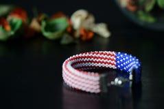 成串珠状在美国国旗的颜色的钩针编织镯子在黑暗的背景的 免版税库存照片