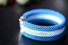 成串珠状蓝色三片树荫钩针编织镯子在黑暗的背景的 免版税库存图片