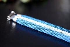 成串珠状蓝色三片树荫钩针编织镯子在黑暗的背景的 图库摄影