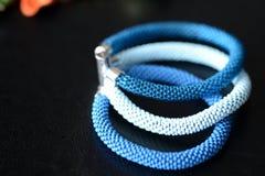 成串珠状蓝色三片树荫钩针编织镯子在黑暗的背景的 免版税库存照片