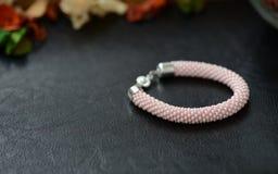 成串珠状钩针编织镯子在黑暗的背景的桃红色颜色 图库摄影