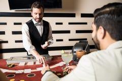 成交卡片的年轻人在赌博娱乐场 图库摄影