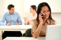 成人亚洲妇女交谈在她的手机 免版税库存照片