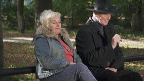 成人人在一名妇女旁边坐公园长椅 股票视频