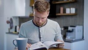 成人人在他的厨房里休息在单独周末的天,翻转杂志页并且读文章 股票录像