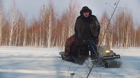 成人人在冬天在微型雪上电车拖车给快速的骑马和运载的乘客穿衣通过随风飘飞的雪  影视素材