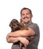 成人人在白色backgroun拿着他的甜小狗被隔绝 免版税库存照片