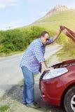 成人人在他残破的汽车附近站立 免版税库存图片