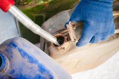 成人人用汽油填装一辆汽车在燃料驻地 免版税库存图片