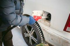 成人人用汽油填装一辆汽车在燃料驻地 图库摄影