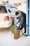 成人人用汽油填装一辆汽车在燃料驻地 免版税图库摄影