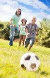 成人使用与足球的夫妇和少年 免版税库存图片