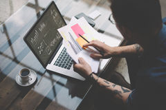 成人刺字了工友与膝上型计算机一起使用在工作场所 商人分析在手上的文件 图表,网上接口 免版税库存图片