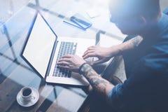 成人刺字了研究有白色空白的屏幕的膝上型计算机的工友在晴朗的办公室 键入的商人  免版税库存图片