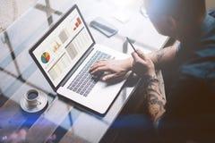 成人刺字了研究移动计算机的商人在晴朗的办公室 键入在笔记本键盘的人 图表和 库存照片