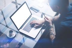 成人刺字了研究移动计算机的商人在晴朗的办公室 键入在笔记本键盘的商人 空白 库存图片
