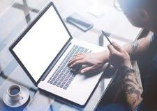 成人刺字了研究移动计算机的商人在晴朗的办公室 键入在笔记本键盘的商人 空白 免版税库存图片