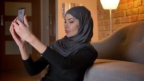 成人可爱的回教女性特写镜头画象做selfies的hijab的在电话,当坐地板时 股票视频