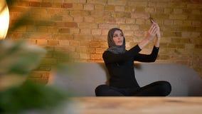 成人可爱的回教女性特写镜头画象采取在电话的hijab的selfies,当坐长沙发时 股票录像