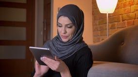 成人可爱的回教女性特写镜头画象hijab冲浪的网的在片剂和微笑上,当坐时 影视素材