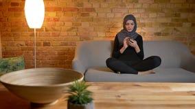 成人可爱的回教女性特写镜头画象hijab的使用电话,当坐长沙发户内在舒适时 股票视频