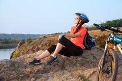 成人可爱的女性骑自行车者休息 免版税库存图片