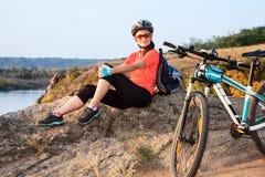 成人可爱的女性骑自行车者休息 免版税图库摄影