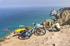 成人可爱的女性骑自行车者在海洋岩石海岸摆在 免版税图库摄影