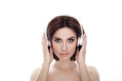 成人可爱的新鲜的看起来的深色的妇女秀丽画象有华美的摆在反对的构成无线耳机突然移动发型的 库存图片