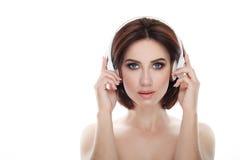 成人可爱的新鲜的看起来的深色的妇女秀丽画象有华美的摆在反对的构成无线耳机突然移动发型的 免版税库存图片