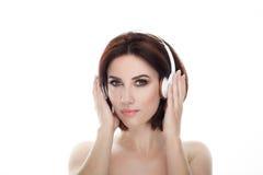 成人可爱的新鲜的看起来的深色的妇女秀丽画象有华美的摆在反对的构成无线耳机突然移动发型的 免版税图库摄影