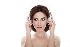 成人可爱的新鲜的看起来的深色的妇女秀丽画象有华美的摆在反对的构成无线耳机突然移动发型的 免版税库存照片