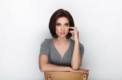 成人可爱的新鲜的看起来的深色的妇女秀丽画象有摆在反对白色背景的突然移动发型的显示情感和 库存照片