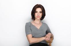 成人可爱的新鲜的看起来的深色的妇女秀丽画象有摆在反对白色背景的突然移动发型的显示情感和 免版税图库摄影