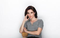 成人可爱的新鲜的看起来的深色的妇女秀丽画象有摆在反对白色背景的突然移动发型的显示情感和 图库摄影