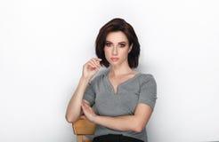 成人可爱的新鲜的看起来的深色的妇女秀丽画象有摆在反对白色背景的突然移动发型的显示情感和 库存图片
