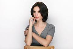 成人可爱的新鲜的看起来的深色的妇女秀丽画象有摆在反对白色背景的突然移动发型的显示情感和 免版税库存图片