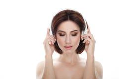 成人可爱的新鲜的看起来的深色的妇女秀丽画象有闭合的眼睛华美的构成无线耳机突然移动发型pos的 免版税库存图片