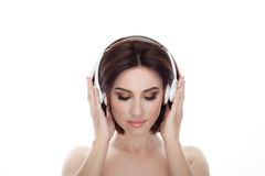 成人可爱的新鲜的看起来的深色的妇女秀丽画象有闭合的眼睛华美的构成无线耳机突然移动发型pos的 免版税库存照片