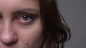 成人可爱的浅黑肤色的男人特写镜头半面孔射击女性与是她的眼睛结束的打开和看照相机 股票录像