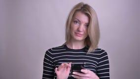 成人可爱的白肤金发的在电话的白种人女性传讯和看微笑与的照相机特写镜头画象  股票录像