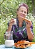 成人吃女性新鲜的房子牛奶饼 免版税图库摄影